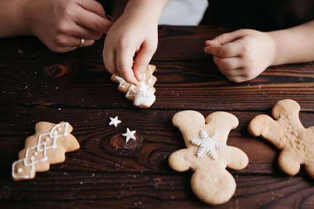 Family home bakery, cooking traditional festive sweets. Christmas and New Year celebration traditions. Mother and daughter decorating Christmas gingerbread cookies Foto de archivo