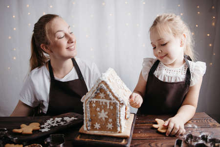 Christmas and New Year celebration traditions. Family home bakery, holiday preparations. Mother and daughter decorating Christmas gingerbread house Foto de archivo