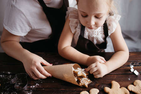 Christmas home bakery, holiday surprise. Mother and daughter packing Christmas gingerbread cookies. Christmas and New Year traditions concept Foto de archivo