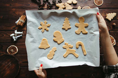Festive food, sweet present, family culinary, Christmas and New Year traditions concept. Mother with cookies of raw gingerbread dough on the pastry board