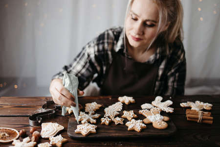 Christmas and New Year celebration traditions. Confectioner decorating gingerbread cookies. Winter holidays, festive sweets