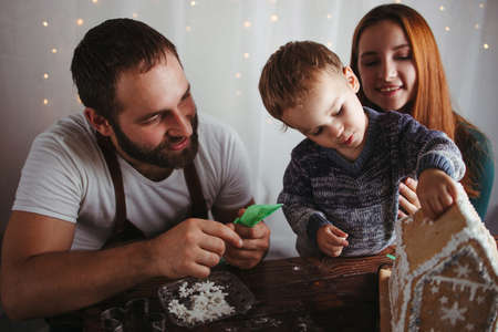 Christmas, family time, holiday preparations. Mother, father and son decorating Christmas gingerbread house Foto de archivo - 155258362