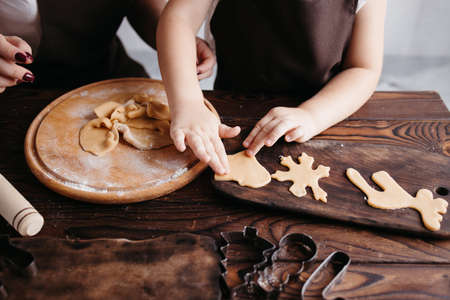 Christmas and New Year holidays, family weekend activities, celebration traditions. Cooking festive homemade sweets. Mother and daughter cutting cookies of raw gingerbread dough
