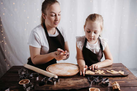 Christmas home bakery. Mother and daughter kneading gingerbread dough with rolling pin