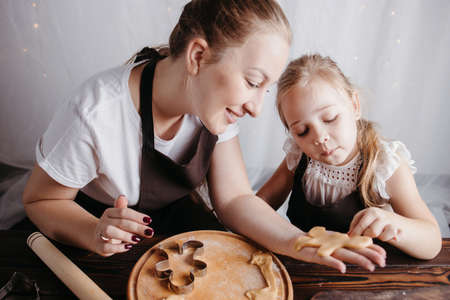 Christmas and New Year holidays, family weekend activities, celebration traditions. Mother and daughter cooking festive homemade sweets. Woman and girl cutting cookies of raw gingerbread dough