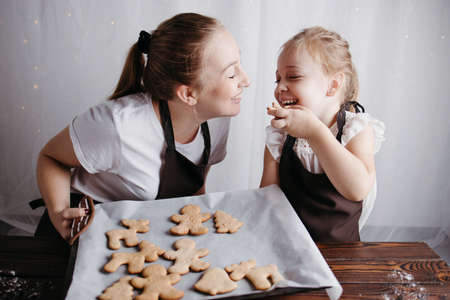 Christmas and New Year traditions concept. Festive food, cooking process, family culinary. Mother and daughter eating fresh gingerbread cookies together