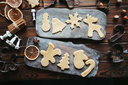 Christmas and New Year celebration traditions. Family home bakery, cooking traditional festive sweets. Gingerbread dough with christmas theme shapes and raw cookies, flat lay