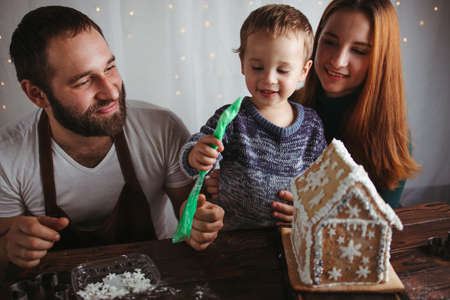 Family values, happy parents, Christmas time. Mother, father and son decorating Christmas gingerbread house