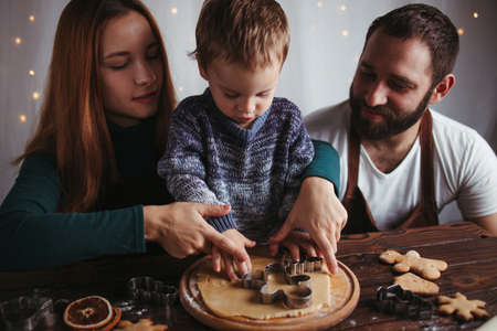 Christmas and New Year holidays, family time, weekend activities, celebration traditions. Mother, father and son making festive homemade gingerbread cookies Foto de archivo