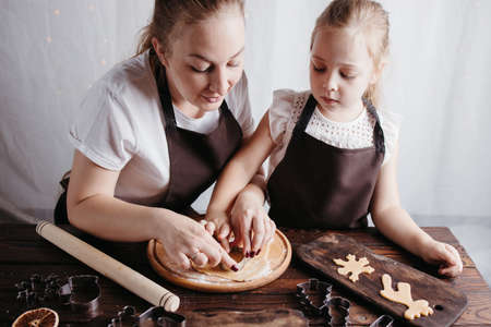 Christmas cooking, festive homemade sweets. Mother and daughter cutting cookies of raw gingerbread dough