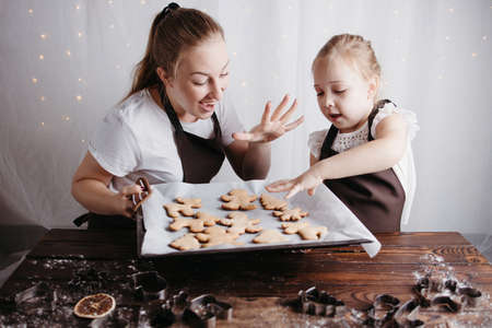 Christmas and New Year traditions concept. Festive food, cooking process, family culinary. Mother and daughter baking fresh gingerbread cookies together Foto de archivo