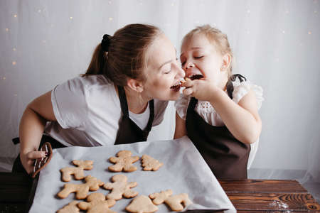 Family time, winter holidays tradition, cooking. Mother and daughter having fun at the kitchen baking gingerbread cookies