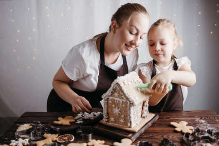 Christmas cooking, festive homemade sweets. Mother and daughter decorating gingerbread house