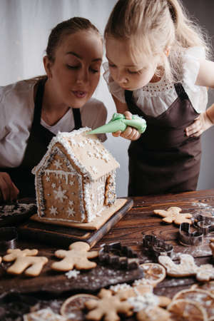 Family home bakery, cooking traditional festive sweets. Christmas and New Year celebration traditions. Mother and daughter decorating Christmas gingerbread house Foto de archivo