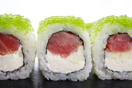 Japanese cuisine, food background. Tasty appetizing sushi rolls with tuna and caviar, copy space