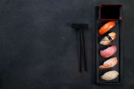 Nigiri sushi set with salmon, grouper, eel, tuna and prawn, flat lay on black plate. Traditional Japanese food, sushi restaurant menu