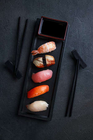 Nigiri sushi set with salmon, grouper, eel, tuna and prawn, flat lay on black plate. Delicious traditional Japanese food, tasty seafood, restaurant concept, food background