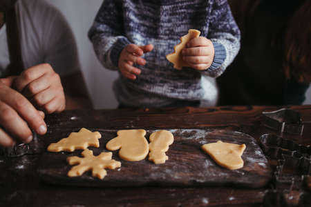 Christmas time, family love. Home weekend. Winter holidays. Family making Christmas gingerbread cookies together