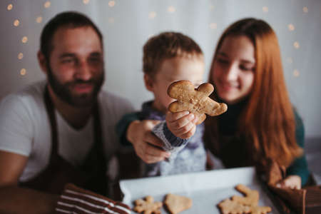 Celebration, New Year, Christmas magic, holiday vibes. Little boy and parents with gingerbread cookies. Family values.