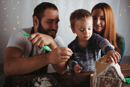 Christmas and New Year celebration. Family time. Holidays. Mother, father and son decorating Christmas gingerbread house Foto de archivo