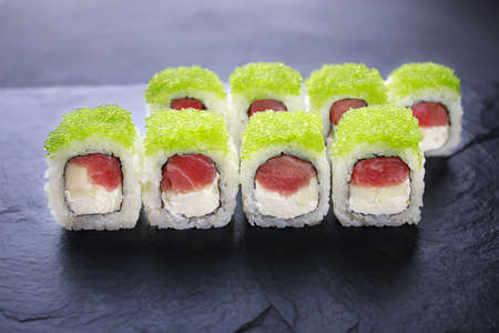 Japanese cuisine, food background. Tasty appetizing sushi rolls with tuna and caviar served on black slate, copy space