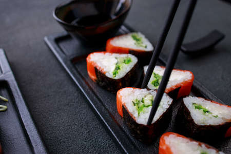Eating sushi. Chopsticks taking salmon maki roll from plate. Food delivery, seafood restaurant concept. Gourmet eating