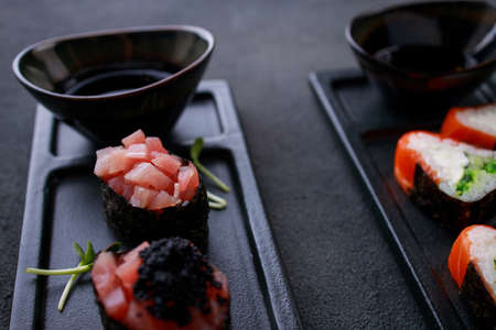 Appetizing gunkan and nigiri sushi set decorated with caviar, served on black plate. Restaurant menu, Japanese food art.