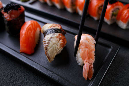 Eating sushi. Chopsticks taking prawn nigiri sushi from plate. Japanese food, deluxe restaurant menu, delicious traditional seafood