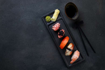 Sushi set. Delicious nigiri sushi on black stone texture background. Top view with copy space. Japanese food restaurant delivery menu Foto de archivo