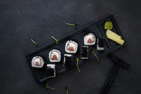 Japanese cuisine, food background. Tasty appetizing sushi rolls with tuna and caviar served on black plate, copy space