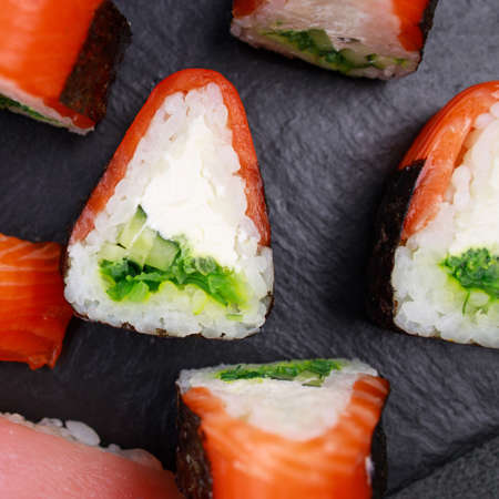 Seafood delicatessen salmon sushi rolls on plate. Food background, goods delivery, Japanese cuisine restaurant menu Foto de archivo