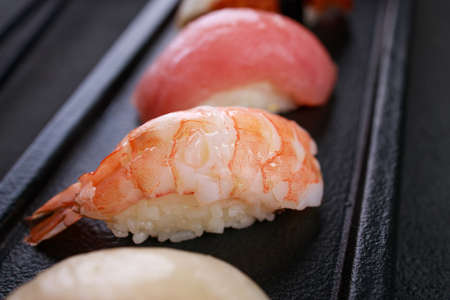 Nigiri sushi set with salmon, grouper, eel, tuna and prawn on black plate. Traditional Japanese food, sushi restaurant menu