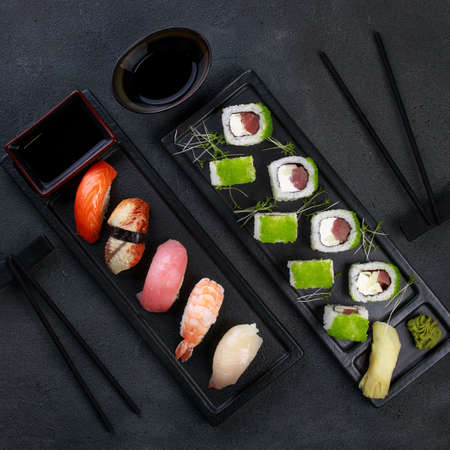 Seafood delicatessen sushi rolls set on plates. Different gourmet snacks. Japanese restaurant menu, food delivery