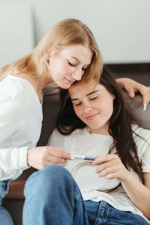Young woman supporting her pregnant friend. Pregnancy, friendship, psychological help, pregnant support group