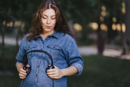 Beautiful pregnant woman holding headphones on her belly. Intrauterine growth, healthy pregnancy, happy maternity, music, motherhood concept Foto de archivo