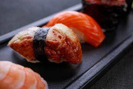 Appetizing gunkan and nigiri sushi set, served on black plate. Restaurant menu, Japanese food art.