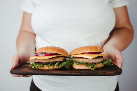 Fast food. Overeating. Weight loss diet, unhealthy eating. Overweight woman with double portion of hamburgers 免版税图像