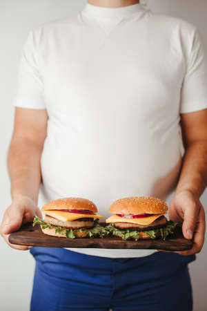 Fast food. Overeating. Weight loss diet, unhealthy eating. Overweight man with double portion of hamburgers