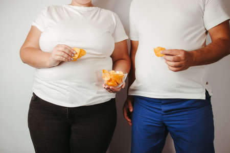 Processed food, unhealthy diet, salt and fat contain. Overweight couple eating salted fattening potato chips 版權商用圖片