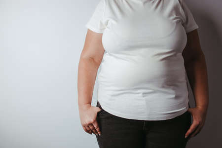 Diet, stress, eating problems, compulsive overeating, weight gain. Overweight woman with big belly, copy space