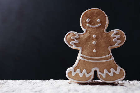 Christmas and New Year traditional attribute, festive sweets for kids, celebration mood. Homemade gingerbread man cookie on dark background