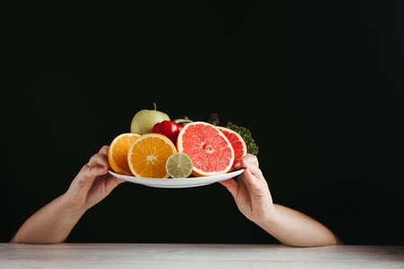 Diet, healthy lifestyle, weight loss, eating habits concept. Hands holding plate with fresh appetizing fruits and vegetables