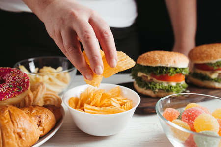 Unhealthy snack, junk food, compulsive overeating. Woman overeating unhealthy meals taking hamburger and chips from plate