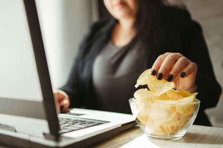 Woman eating junk food, snacking with chips Standard-Bild