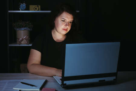 Young focused woman doing overtime job at night Фото со стока