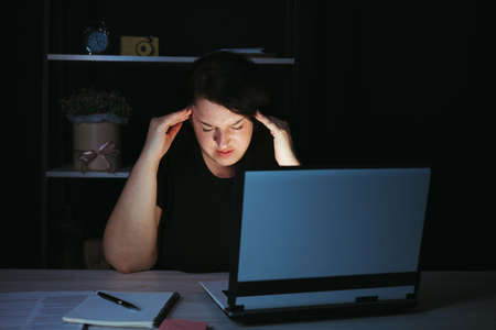Tired exhausted woman working with laptop at night