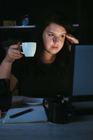 Woman drinking too much coffee at night work