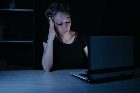 Young focused woman doing overtime job at night Stock Photo