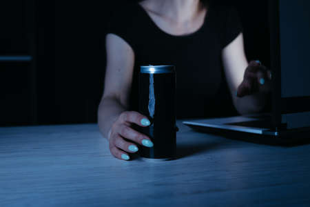 Focused woman drinking energy drink at night Stock Photo