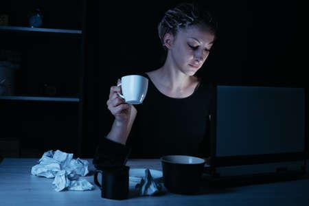Night work. Woman drinking coffee working late